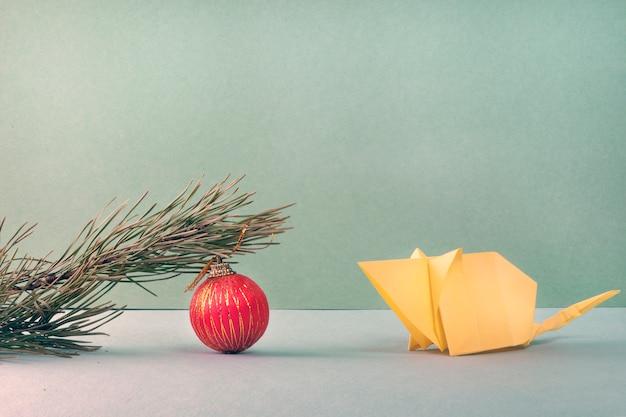 折り紙技術を使用して作成されたホワイトペーパーマウスは、赤いボールで松の枝を見てください。