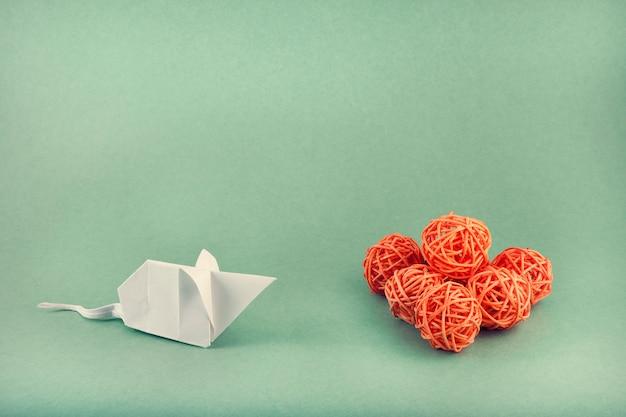 折り紙の技法を使用して作成されたホワイトペーパーマウスがオレンジ色のボールを見る