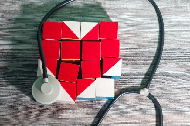 不健康な赤いハートの形をした立方体のモザイクで、医療用の検鏡を注意深く囲みます。医学、ケアの概念。
