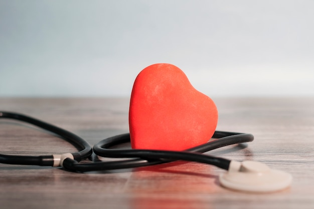 木製のテーブルの上に横たわる赤いハート、慎重にスタトスコープと絡み合っています。ケア、支援、医学の概念。