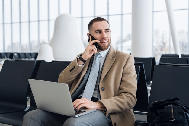 ラップトップに取り組んで、空港の待合室で携帯電話で話している幸せなビジネスマン。空港ターミナルの待合室でハンサムな白人実業家