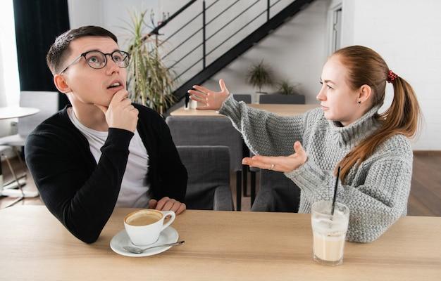 若いカップルがカフェで主張しています。