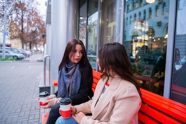 Молодая женщина пытается объяснить что-то своему другу, попивая кофе в кафе