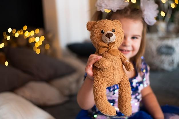 Веселая маленькая девочка играет со своей пушистой игрушкой