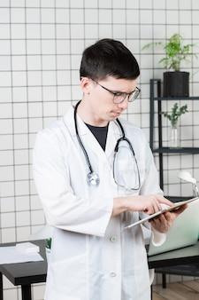 タブレットコンピューターを使用して物思いにふけるハンサムな若い男性医師。