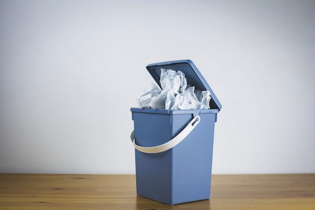 灰色のゴミ箱はしわくちゃの紙でいっぱい