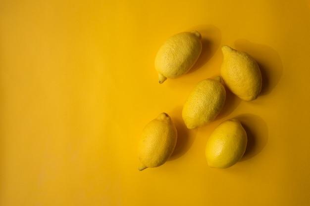 黄色い紙の背景に黄色いレモン。上面図。