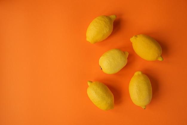 Желтые лимоны на оранжевом фоне. вид сверху