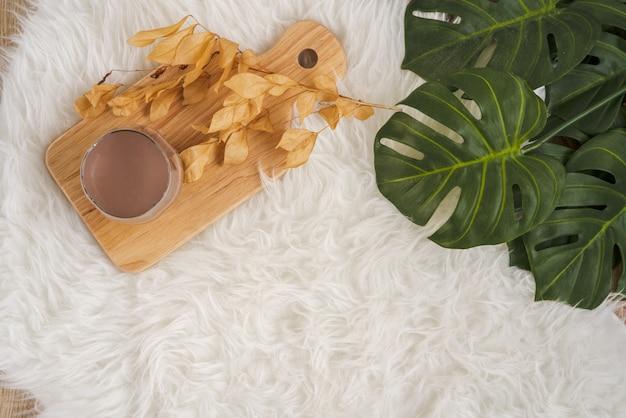 Стакан теплого шоколадного молока на деревянной доске на белом пушистом меховом коврике, готовый к хорошему зимнему дню