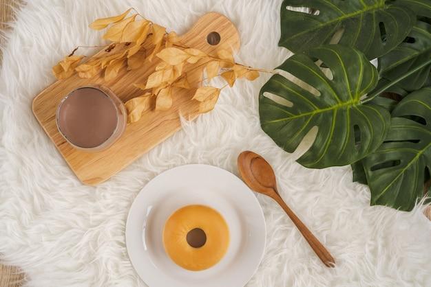 Вкусный пончик в белой тарелке рядом с деревянной ложкой со стаканом теплого шоколадного молока на деревянной доске, на белом пушистом меховом коврике, готовом к завтраку