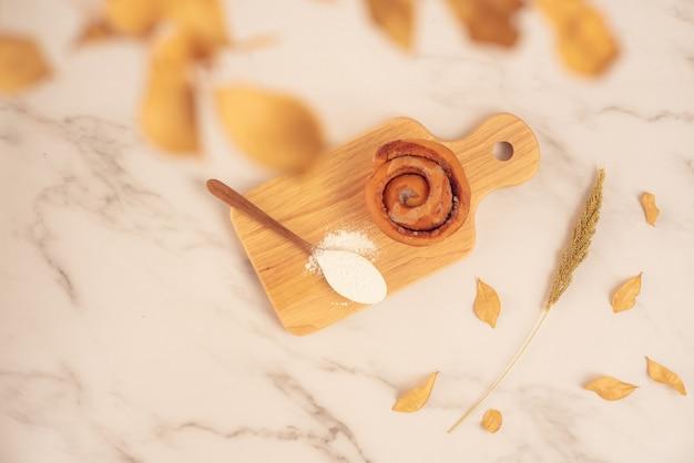 Свежая выпечка, свежая булочка с корицей с ложкой муки на деревянной доске на белой мраморной поверхности. вкусный вкусный десерт, французский завтрак. вид сверху