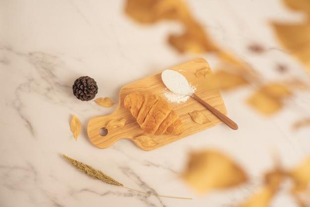 Свежая выпечка, свежий круассан с ложкой, полной муки на деревянной доске на белой мраморной поверхности. вкусный вкусный десерт, французский завтрак. вид сверху