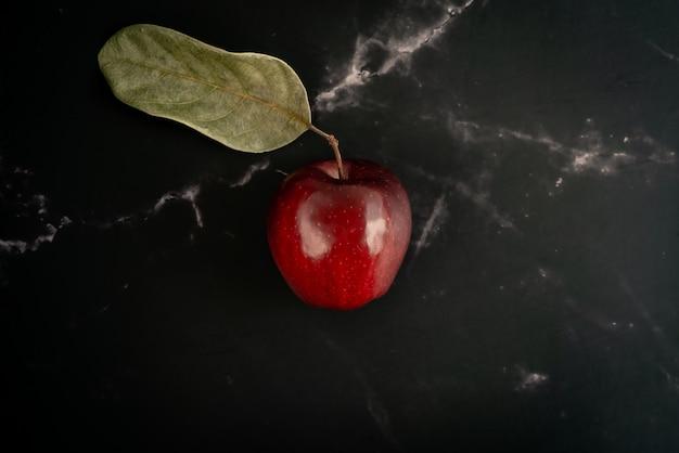 Свежее красное яблоко с зелеными листьями лежат на черном фоне мрамора. вид сверху плоская планировочная композиция.
