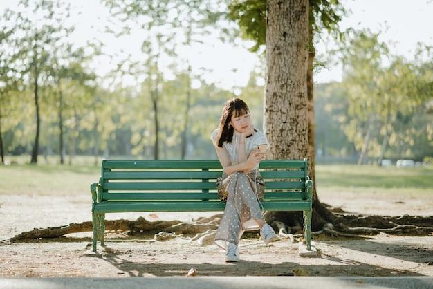 Довольно азиатские леди в белых одеждах, сидя со скрещенными ногами на скамейке, расслабиться и слушать музыку со своего телефона