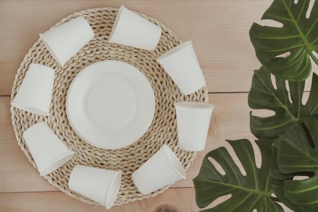 紙の食品包装、環境に優しい使い捨て、堆肥化、リサイクル可能な紙コップと植物の枝が付いたプレート。コピースペースのトップビュー。廃棄物ゼロのコンセプト