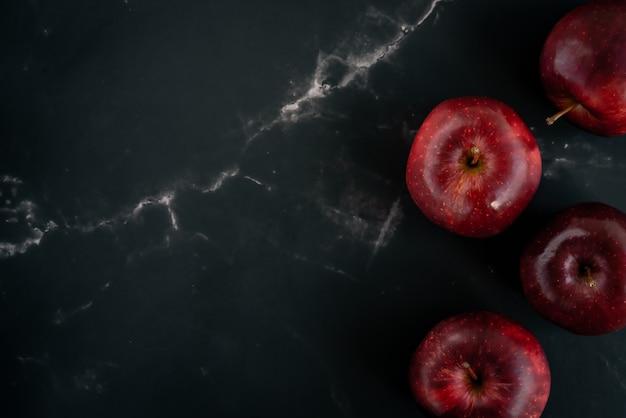 Свежие красные яблоки лежат на черном фоне мрамора. вид сверху плоская планировочная композиция. пространство для текстового шаблона