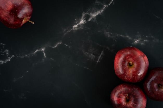 Свежие сочные красные яблоки на черной мраморной поверхности. вид сверху плоская планировочная композиция. пространство для текстового шаблона