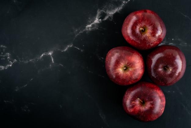 Группа в составе свежие сочные красные яблоки на черной мраморной поверхности. вид сверху плоская планировочная композиция. пространство для текстового шаблона