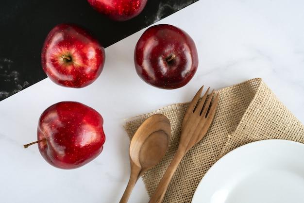 Свежие сочные красные яблоки лежат на черно-белой мраморной поверхности с деревянной ложкой и вилкой, пустой белой тарелкой на вретище. вид сверху плоская планировочная композиция.