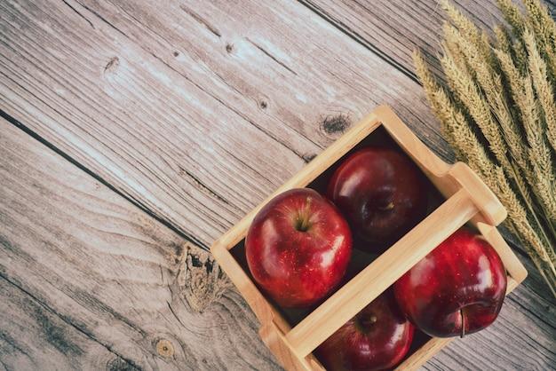 Деревянная корзина со свежими красными яблоками и куча ушей спелых зерен пшеницы на старой деревянной поверхности доски. вид сверху плоская планировочная композиция. пространство для текстового шаблона
