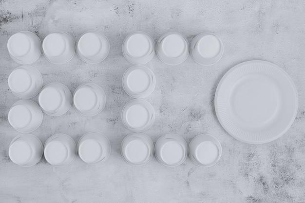 環境に優しい紙皿とカップは、粗い表面にエコという言葉で配置されています。持続可能なコンセプト。上面図。ミニマリストスタイル。