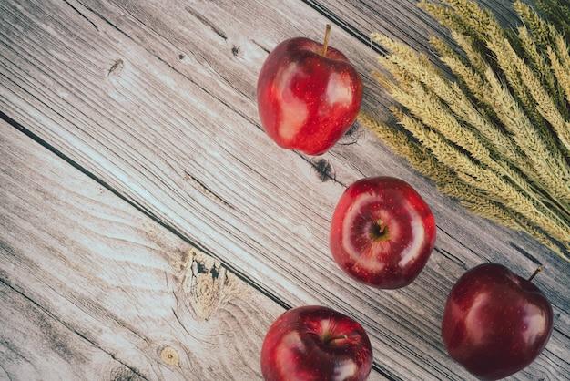 Свежие красные яблоки и куча ушей спелых зерен пшеницы на старой деревянной доске поверхности. вид сверху плоская планировочная композиция. пространство для текстового шаблона