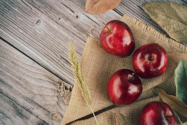 Свежие сочные красные яблоки с травой зерна пшеницы и много сухих листьев лежат на мешковине на старой деревянной поверхности доски. вид сверху плоская планировочная композиция. пространство для текстового шаблона