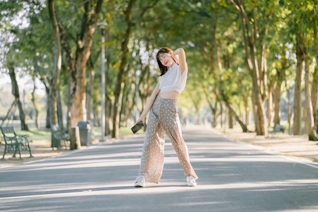Счастливая азиатская молодая дама в белых одеждах представляя стоять на тротуаре слушая музыку от ее телефона с ее глазами закрыла в настроении ослабляя на природе с солнечным светом в парке