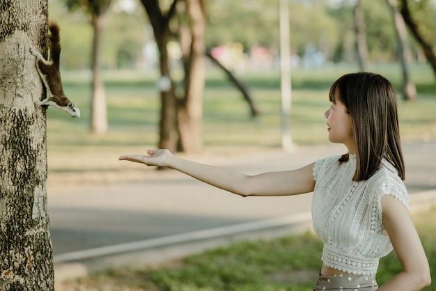 Молодая азиатская усмехаясь женщина в белых одеждах передала гайки коричневой белке стоя на дереве найденном случайно во время гулять в парке на природе