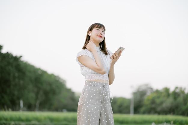 Молодая усмехаясь женщина в белых одеждах при наушники стоя в парке пока использующ мобильный телефон слушая к музыке ее глазами смотря что-то интересное в настроении ослабляя и счастливое