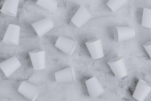 粗い表面に置かれた多くの環境に優しい紙コップ。持続可能なコンセプト。上面図。ミニマリストスタイル。