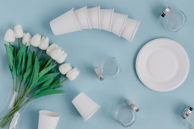水色のテーブルに置かれた環境にやさしい素材の紙製食品包装とガラス製品。使い捨て、堆肥化、リサイクル可能な紙コップとプレート。上面図。プラスチックを使わず廃棄物ゼロの概念