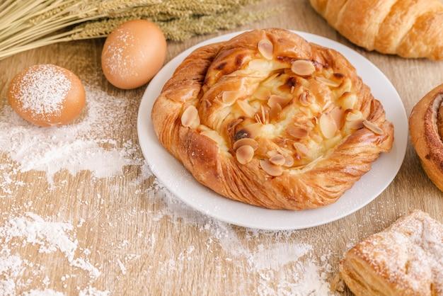 木製テーブルの表面上の小麦粉、さまざまな焼きたてのパン、小麦、卵の調理組成