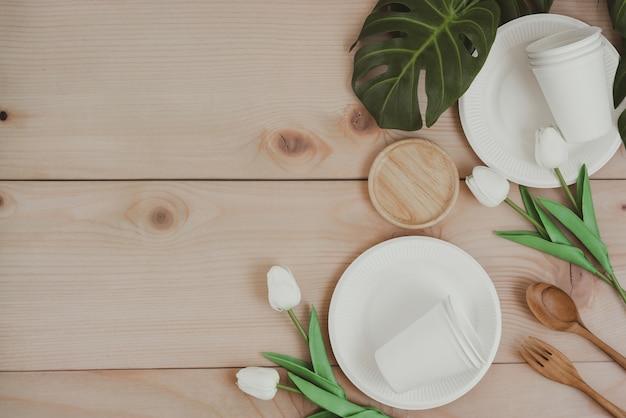 紙の食品包装、環境に優しい使い捨て、堆肥化、リサイクル可能な紙コップ、木製の背景に植物の枝を持つプレート。コピースペースのトップビュー。廃棄物ゼロのコンセプト