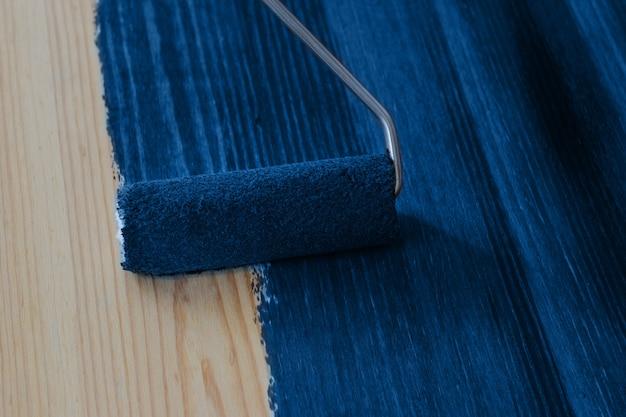 古典的な青い色のローラーブラシで木板を塗る