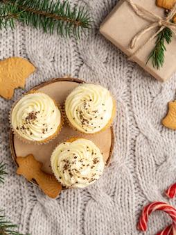 クリスマスと冬のデザート、クリームチーズのフロスティングとチョコレートのジンジャーブレッドカップケーキ。シナモンのフレーム、紙で覆われたプレゼントギフトボックス、小ぎれいなな枝、キャンディー杖。フラットレイアウト、静物