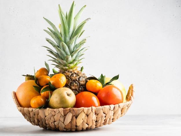 Фрукты в корзине изолированы. свежий ананас, мандарины, грейпфрут, конфетка, груши и плоды хурмы. белый фон.