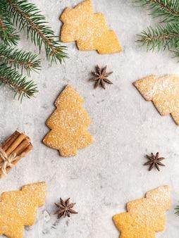 Традиционные пряники и медовое печенье, форма рождественской елки, ветви ели, звезды аниса, палочки корицы и сахарная пудра. зимняя и рождественская открытка, белая.