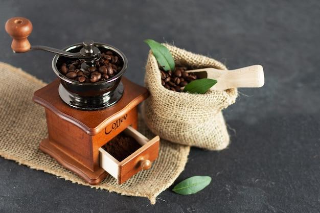 Ручная винтажная кофемолка и кофейные зерна в мешочке из ткани на деревянном столе.