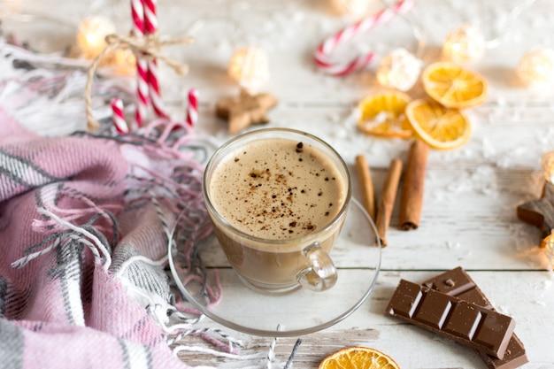 カプチーノまたはホットミルクチョコレートのホットカップと乾燥オレンジフルーツとシナモン。