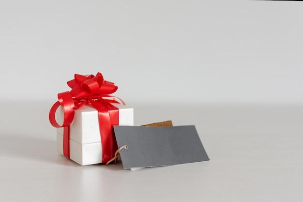 テーブルの上の空白のグリーティングカードとギフトボックス。バレンタインや誕生日のコンセプト。