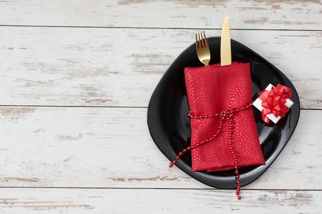 ゴールデンフォークとナイフと装飾でバレンタインデーのお祝いテーブルの設定。