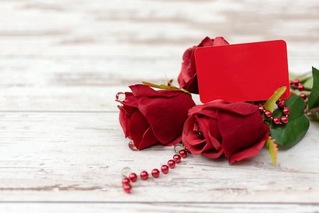 Валентина или юбилейный подарок с букетом красивых красных роз и прикрепленный красный пустой подарок тег для вашего текста.