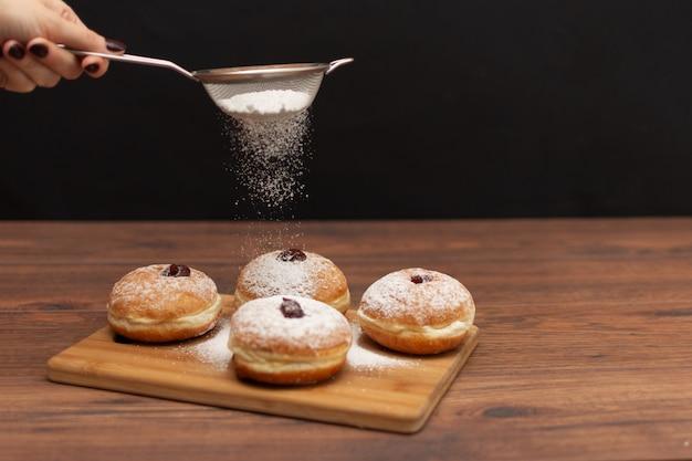 ハヌカ・スフガニヨット。ハヌカの伝統的なユダヤ人ドーナツと赤ジャムと砂糖の粉。