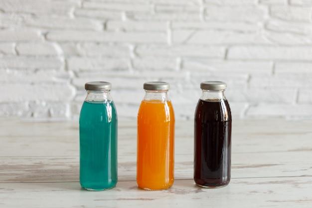 等張性エネルギードリンク。さまざまな味のスポーツ飲料のボトルと木製のテーブルに追加された昆布茶。