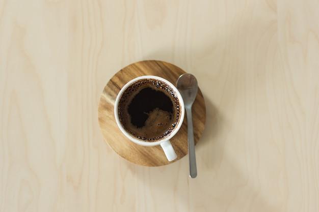 木製のテーブルの上のコーヒーカップとソーサー。