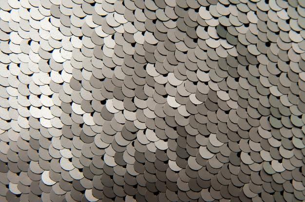 銀の光沢のあるスパンコールクローズアップマクロ抽象的な表面のテクスチャ背景。スパンコール付きのファッショナブルな高価な明るい生地。