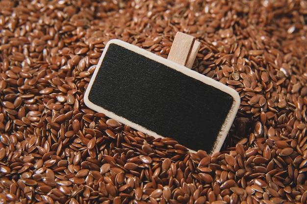 亜麻の種子の表面とテキスト用の小さな黒板。健康のためのスーパーフード。