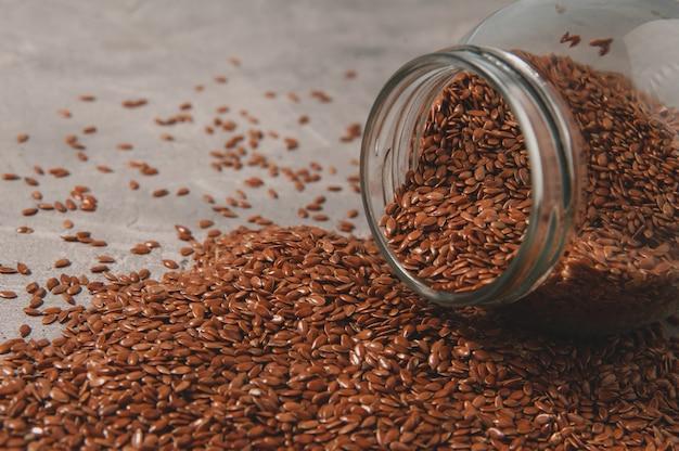 Стеклянная банка с семенами льна на серой поверхности. здоровая пища.