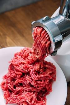 肉挽き器-肉を挽くプロセス。ミンチマシンの牛ミンチ。